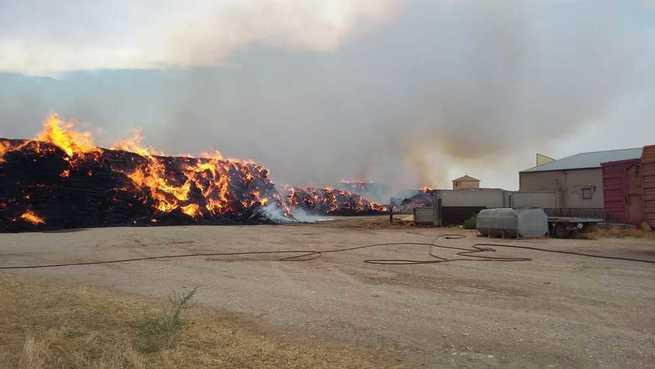 Efectivos del SEPEI permanecerán toda la noche realizando labores de vigilancia y refresco de la nave de ganado afectada por un incendio de balas de paja en La Gineta