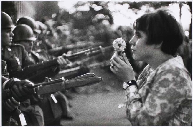 imagen de Muchacha ofreciendo una flor a los soldados.