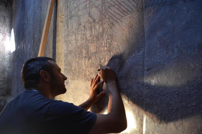 Un arqueólogo calca los dibujos de las paredes de la mazmorra de Calatrava La Vieja. Foto: M.C.